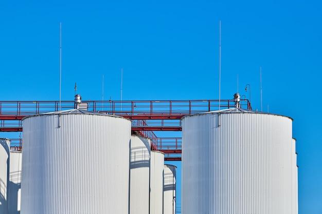 Белые баки для хранения топлива на фоне голубого неба. большие промышленные цистерны белого цвета с лестничным доступом для бензина и масла, емкости для жидких металлов. импорт экспорт.