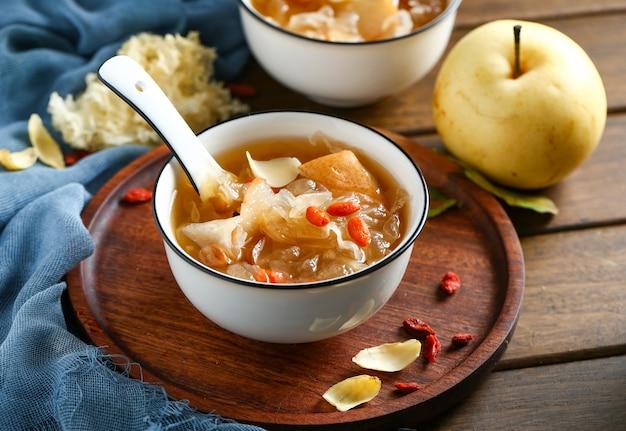나무 접시에 흰색 그릇에 흰색 곰팡이 수프와 배