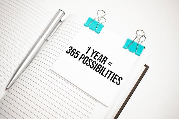 Белый калькулятор будущего, лист бумаги, розовые скрепки и ручка серебристого цвета. текст 1 год 365 возможности