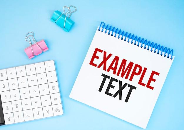 白い未来の電卓、紙のシート、ピンクのペーパークリップ、銀色のペン。テキスト例テキスト