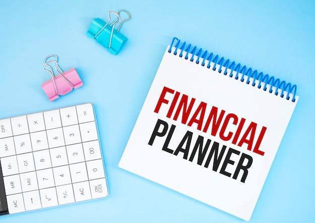 白い未来の電卓、紙のシート、ピンクのペーパークリップ、銀色のペン。テキストファイナンシャルプランナー
