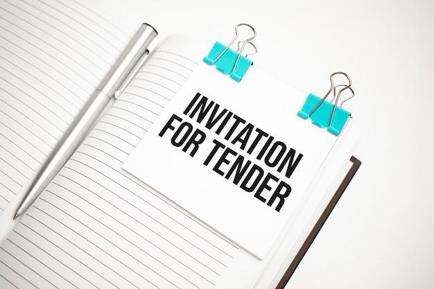 Белый калькулятор будущего, лист бумаги, розовые скрепки и ручка серебристого цвета. sms-приглашение на тендер