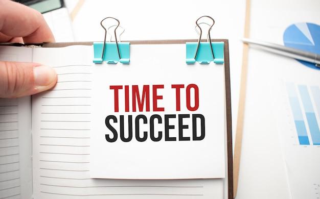 Белый калькулятор будущего, лист бумаги, розовые скрепки и ручка серебристого цвета. текст пора добиться успеха
