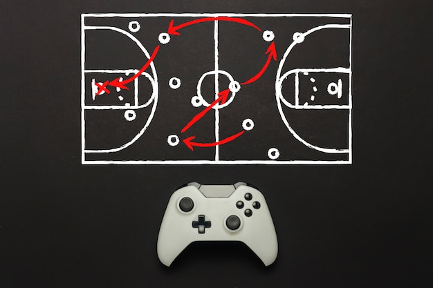 White gamepad on a black background. added a basketball field scheme. tactics of the game. concept game of basketball on the console, computer games. flat lay, top view.