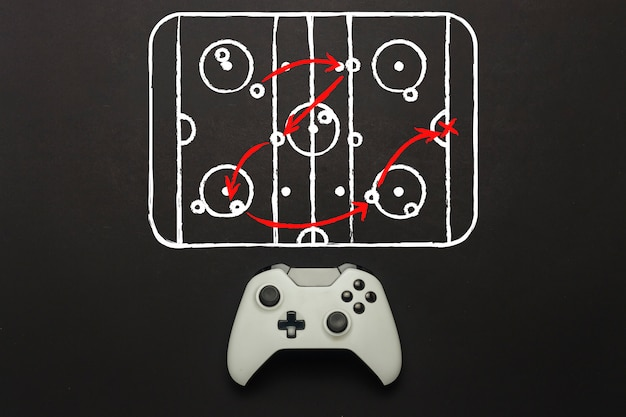 White gamepad on a black background. added hockey court scheme. tactics of the game. concept game of hockey on the console, computer games. flat lay, top view.