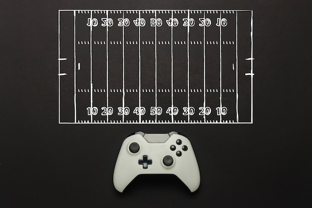 White gamepad on a black background. added a soccer field scheme. tactics of the game. concept game of american football on the console, computer games. flat lay, top view.