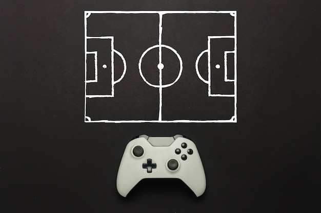 White gamepad on a black background. added a soccer field scheme. tactics of the game. concept game of football on the console, computer games. flat lay, top view.