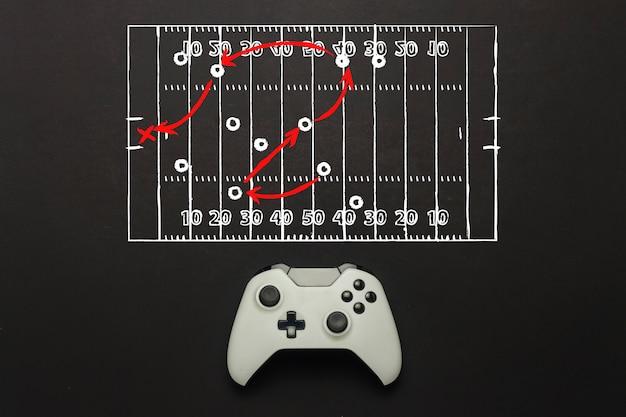 Белый геймпад на черном фоне. добавлена схема футбольного поля. тактика игры. концепция игры в американский футбол на консоли, компьютерные игры. плоская планировка, вид сверху.