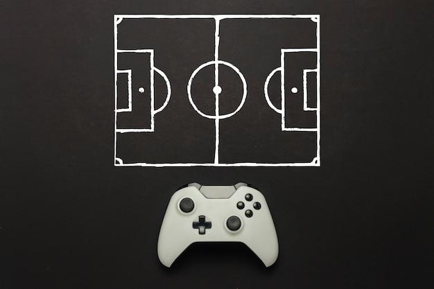 Белый геймпад на черном фоне. добавлена схема футбольного поля. тактика игры. концепция игры в футбол на консоли, компьютерные игры. плоская планировка, вид сверху.