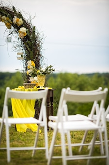 White garden chairs stand before wedding altar made of osier