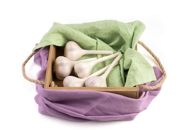 分離された白いニンニク、側面図、色付きのナプキンが付いた木箱に美しくパッケージされています。食品と農産物のコンセプト。