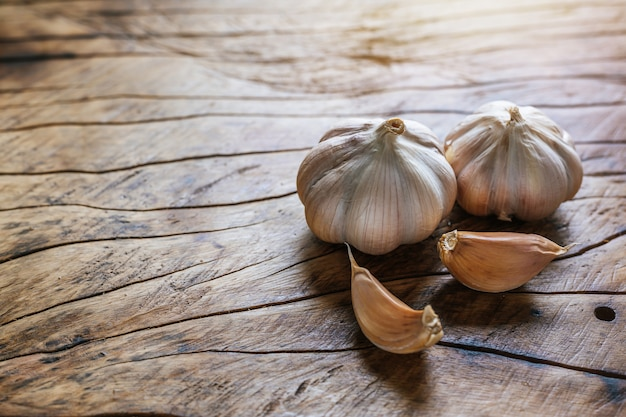 White garlic placed on a dark brown wood floor.