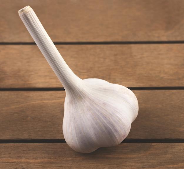 白いニンニクの側面図、木製のテーブルの上に配置。食品と農産物のコンセプト。