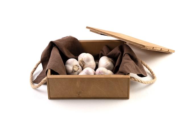 Деревянная коробка белого чеснока на изолированной льняной салфетке