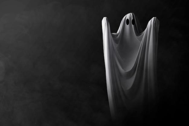 暗い背景で出没する白い幽霊。ハロウィーンのコンセプト