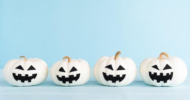Белая тыква-призрак на пастельно-синем фоне. концепция украшения хэллоуина.