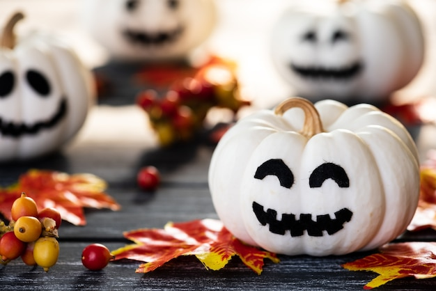 White ghost pumpkins with colorful autumn leaves on a black wooden table background.