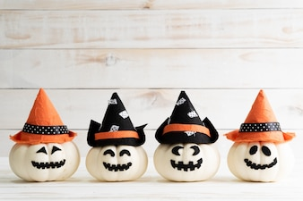 White ghost pumpkins with witch hat on white wooden board background with bat.