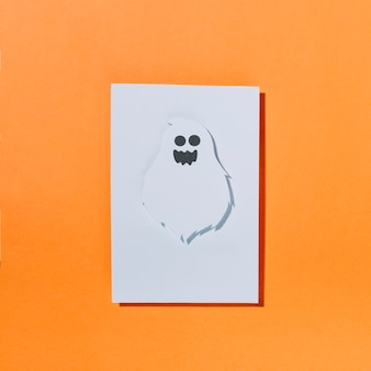 White ghost with funny face on sheet of paper