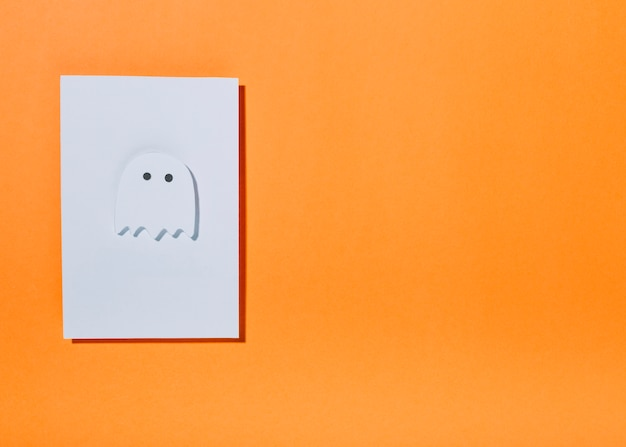 White ghost with little eyes on sheet of paper
