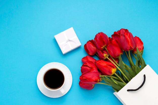 白いギフトバッグ、小さな白いギフトボックス、ブラックコーヒーと白いカップ、ブルーの赤いチューリップの花束。コンセプトエンゲージメントまたは結婚、ショッピングを提供