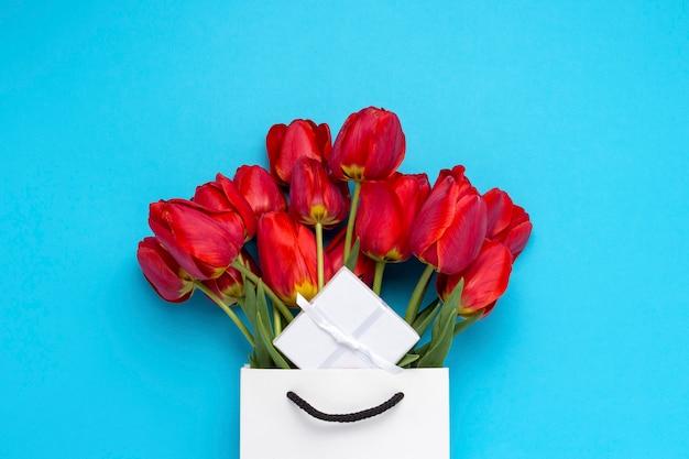 Белая подарочная сумка, маленькая белая подарочная коробка и букет красных тюльпанов на синем. концепция предлагает помолвку или брак, шоппинг