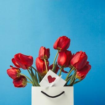 Белая подарочная сумка, маленькая белая подарочная коробка с сердечком и букет красных тюльпанов на синем. концепция предлагает помолвку или брак