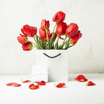 Белая подарочная сумка, маленькая белая подарочная коробка и букет красных тюльпанов на светлом камне. концепция предлагает помолвку или брак
