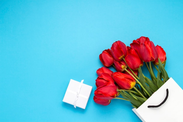 White gift bag, a small white gift box and a bouquet of red tulips on a blue background.
