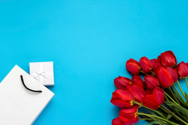 White gift bag, a small white gift box and a bouquet of red tulips on a blue. concept offers an engagement or marriage, shopping