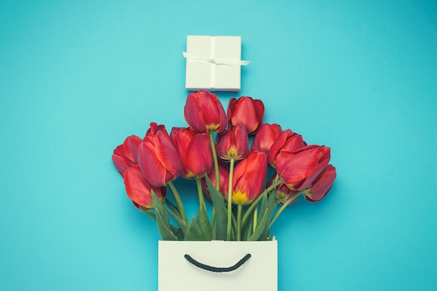 White gift bag, a small white gift box and a bouquet of red tulips on a blue