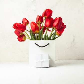 White gift bag, small white gift box, petals and bouquet of red tulips on a light stone. concept of an offer for an engagement or a marriage