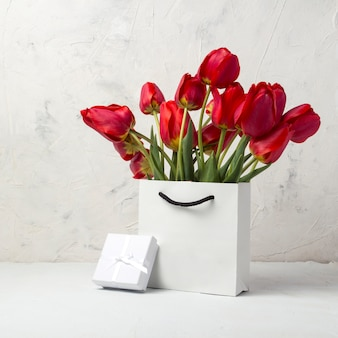White gift bag, small white gift box, petals and bouquet of red tulips on a light stone. concept offer a gift or an engagement, marriage