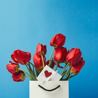White gift bag, a small white gift box with a heart and a bouquet of red tulips on a blue. concept offers an engagement or marriage
