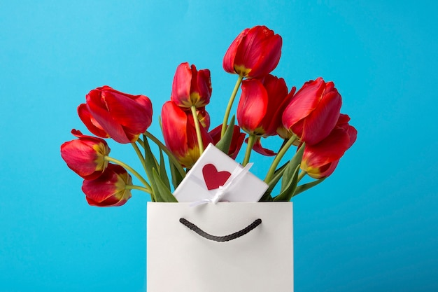 White gift bag, a small white gift box with a heart and a bouquet of red tulips on a blue