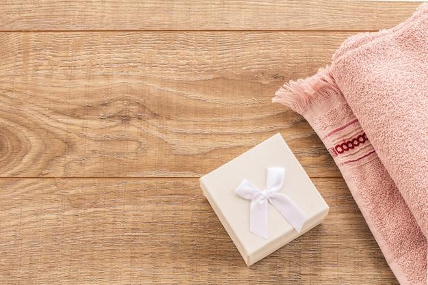 나무 배경에 흰색 선물 상자와 부드러운 테리 수건. 스파 및 바디케어 세트입니다. 휴일 인사말 개념입니다. 평면도.