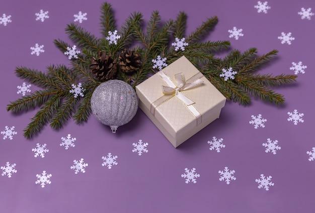 白いギフトボックスのモミの枝クリスマスの光沢のあるボールと雪片