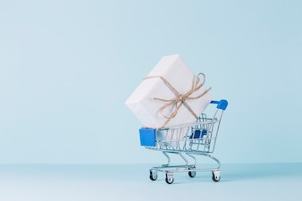 White gift box in shopping cart on blue backdrop