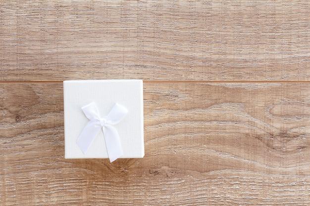 木の板に白いギフトボックス。上面図。休日に贈り物をするという概念。