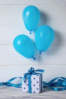 White gift box or present with blue ribbon and balloons for birthday party