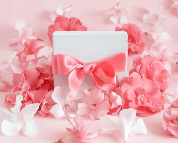 핑크 꽃 사이 활과 흰색 선물 상자를 닫습니다.