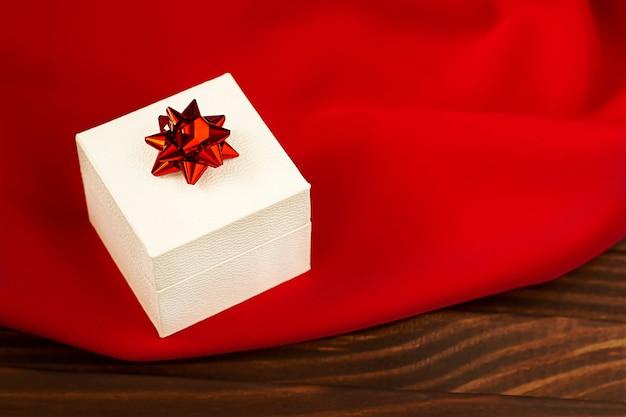 美しい緋色の生地に赤いリボンが付いた白いギフトボックス