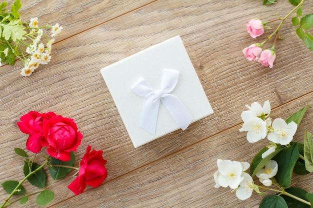木製の背景に美しいバラ、ジャスミン、牡丹、カモミールの花と白いギフトボックス。休日に贈り物をするという概念。上面図。