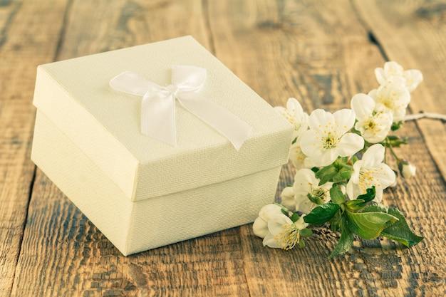 木製の背景に美しいジャスミンの花の枝と白いギフトボックス。休日に贈り物をするという概念。
