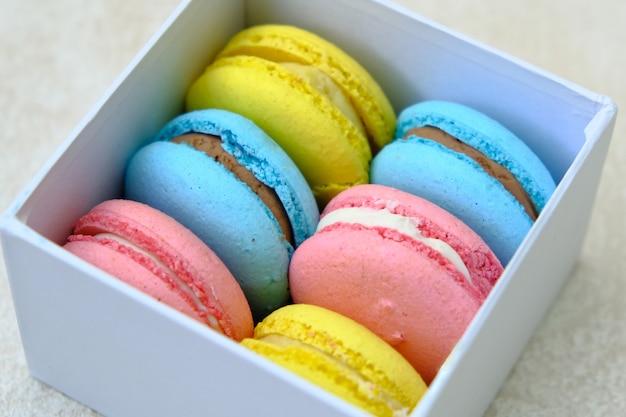 カラフルなフランスの甘いペストリーマカロンと白いギフトボックス。カフェやベーカリーの広告用。