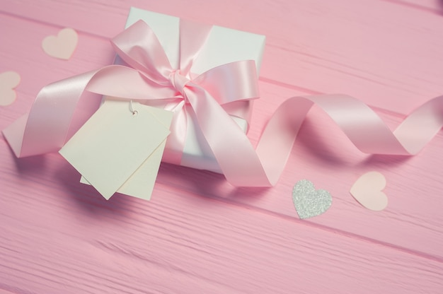 White gift box with a pink satin bow and ribbon on pink table