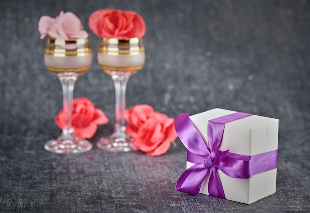 White gift box with purple ribbon, glasses and roses on gray background
