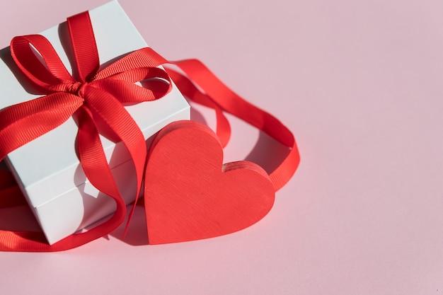 バレンタインデーのピンクの背景に赤いリボンと赤いハートの白いギフトボックス。お誕生日おめでとう、結婚式、グリーティングカード、愛のシンボル。感情の表示
