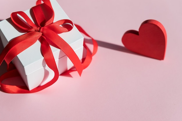 White gift box with red bow ribbon and red heart on pink background for valentines day
