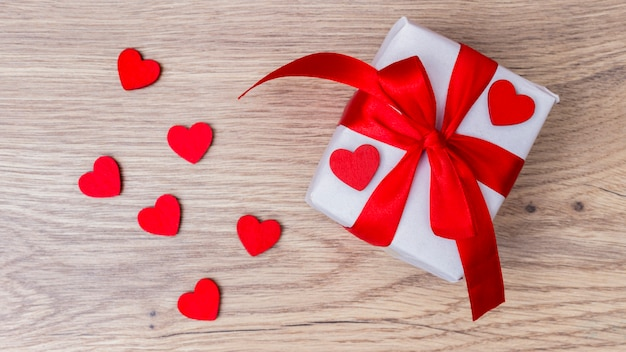 White gift box with red hearts on table